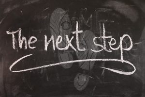 """Chalkboard with """"the next step"""" written on it and footprints on board"""